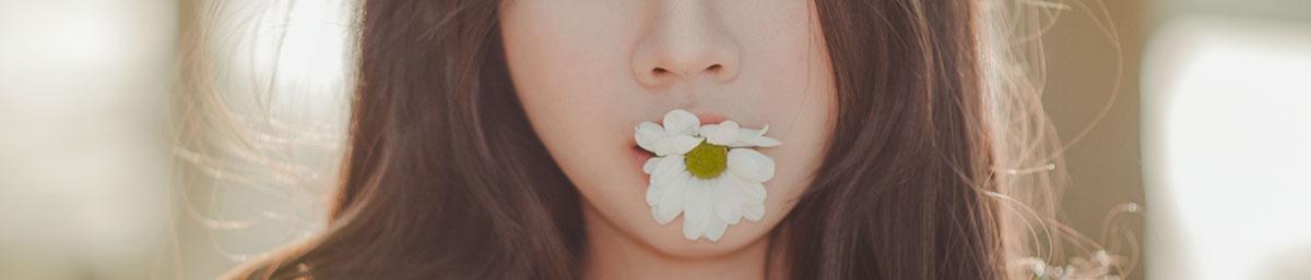 Ромашка во рту у девушки с красивыми волосами после безсульфатного шампуня.